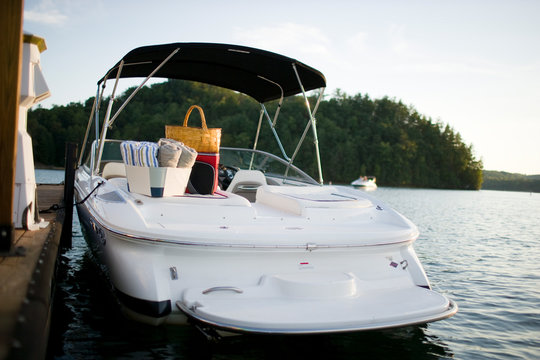 Boat with towels and a picnic basket on a lake.