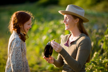 Mid-adult woman with her young daughter picking an aubergine while on a farm.