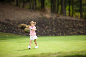 Young girl pulling off glove on golf course