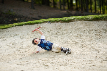 Young boy lying in the sand trap on golf course