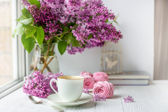 Bouquet of lilacs, cup of coffee, homemade marshmallow and stack of books. Romantic spring morning. Selective focus