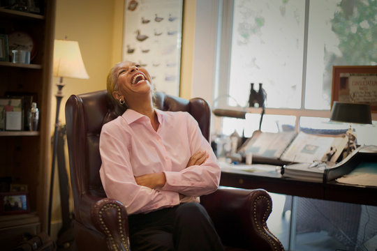 Mature woman laughing while sitting in an armchair next to her desk.