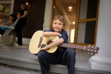 Portrait of a boy holding an acoustic guitar while sitting on a porch step.