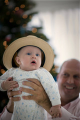 Portrait of a young baby wearing a hat while held aloft by his smiling father.