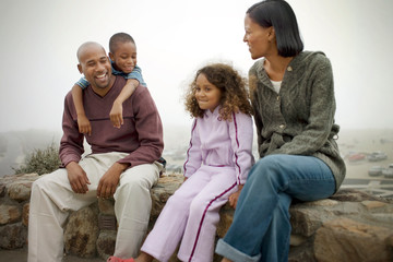 Happy mid-adult couple and their two young children sitting on a stone wall outdoors.