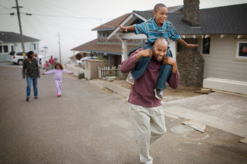 Father carrying his young son on his shoulders down a suburban street.