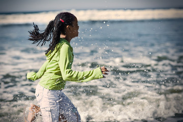 Girl running through water at a beach.