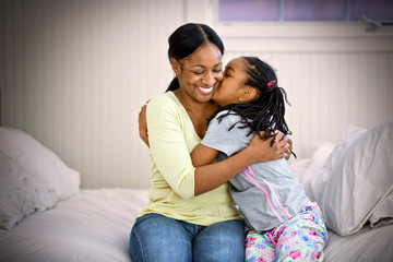 Smiling mid-adult woman being kissed on the cheek by her daughter while sitting with their arms around each other on a bed.