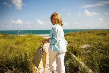 Mature adult woman running towards the ocean at a beach.