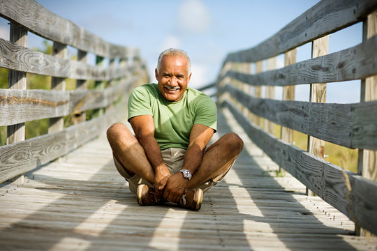 Portrait of a smiling mature adult man sitting with crossed legs on a wooden path.