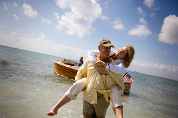 Smiling mature man piggybacking his wife from a boat to the shore on a beach.