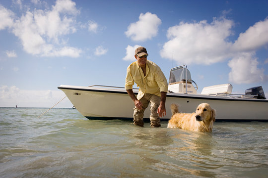 Smiling man standing next to his boat in shallow water with his dog.