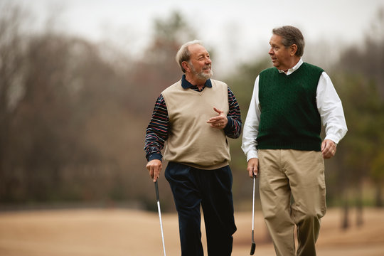 Two men carrying golf clubs walking and talking.