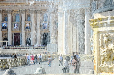 The ancient fountain surrounded by tourists. St. Peter's Square is located in front of St. Peter's Basilica in the Vatican City.
