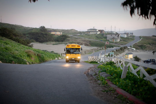 School bus driving along a rural road at sunset.