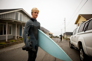 Portrait of a teenage boy holding a surfboard on a road.