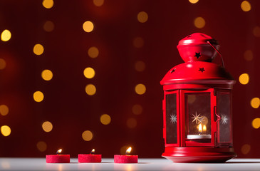 Lantern with candles on a shiny light dark red background