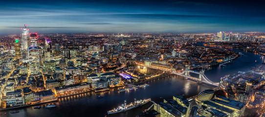 Fotomurales - Weites Panorama der hell beleuchteten Skyline von London entlang der Themse am Abend, Großbritannien