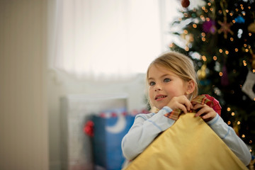 Young girl opening a present on Christmas Day.