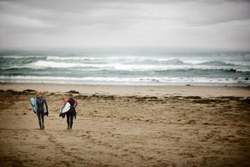 Two teenage boys holding surfboards walking across a beach.