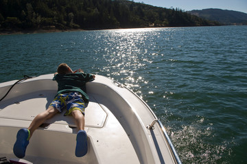 Boy lying on a boat looking out at the water.