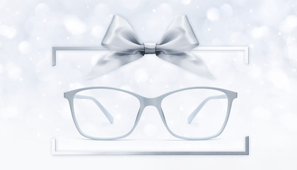 eyeglasses gift card, grey spectacles and silver ribbon bow in box frame isolated on blurred lights  background