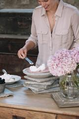 Person spreading cream on cake
