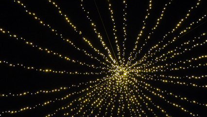 Strings of yellow lights spreading out from a center against the dark background