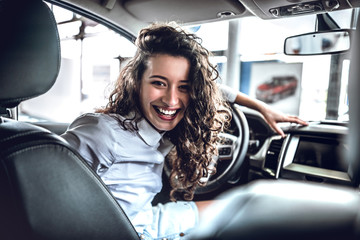 Portrait of beautiful young woman inside in new car Wall mural