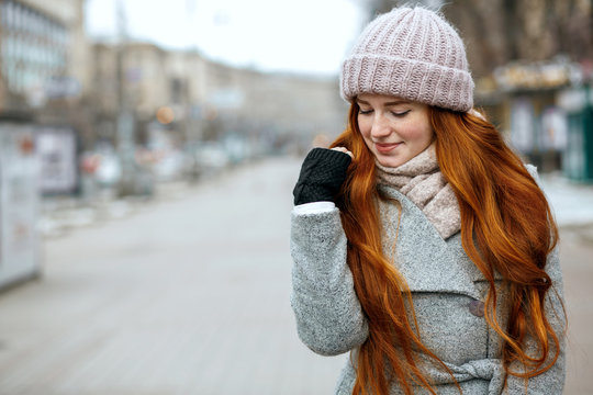 Closeup shot of amazing ginger model with long hair wearing knitted cap and scarf walking at the city. Empty space
