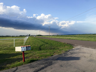 Oklahoma Storm Rolling In Along Country Road with Mailbox and White Fence.