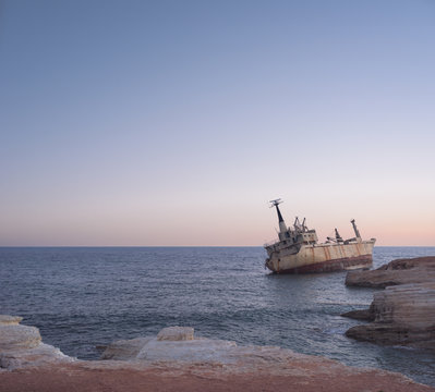 Fishing boat wreck floating on the sea in the sunset
