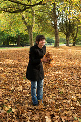 Young woman playing with leaves in a park