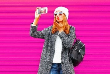 Pretty young woman taking selfie by smartphone blowing red lips sends an air kiss in coat jacket, white knitted hat on colorful pink wall background