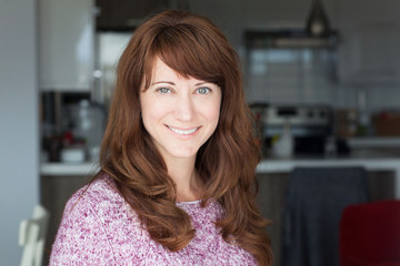 Closeup of a pretty red woman smiling in a kitchen