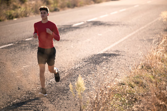 Handsome young man running on the road in the countryside.