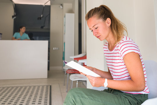 Female patient reading an informative flyer in orthodontic clinic
