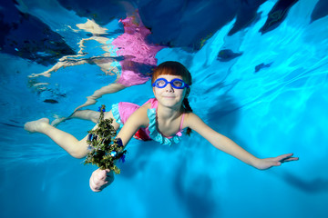 Cute little girl swims and poses under the water with a Christmas tree in her hand, in a pink swimsuit and swimming glasses on a blue background. She looks at the camera and smiles. Portrait