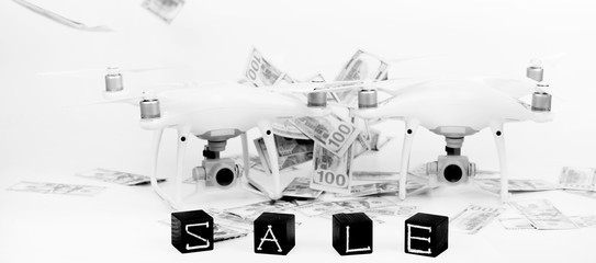 "Flying drones on a white background with inscriptions ""sale"". On the background of money"