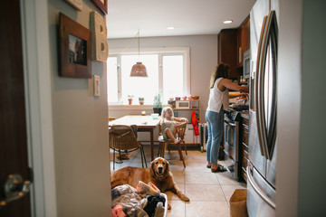Mom cooking dinner with daughter and dog