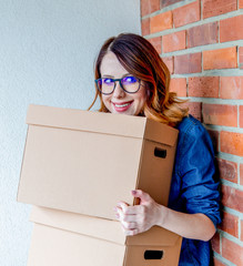 young redhead woman in jeans shirt standing on brick wall with moving boxes. European ethnicity