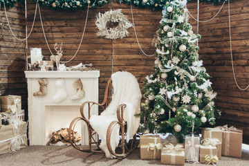 Christmas decorations: rocking chair, Christmas tree, fireplace with socks, gifts on the background of a wooden wall. Christmas Photo Zone. New year photo zone with fireplace and fir tree.