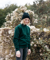 lifestyle portrait of young adult woman wearing green sweater in front of fall foliage