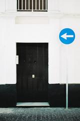Black door and direction arrow