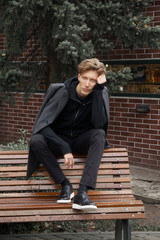 Stylish young man posing on bench