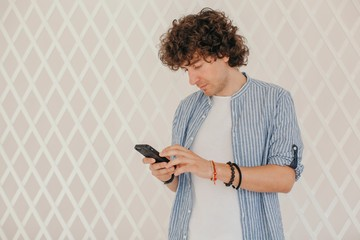Curly brunet checking messages or typing something with his phone indoors