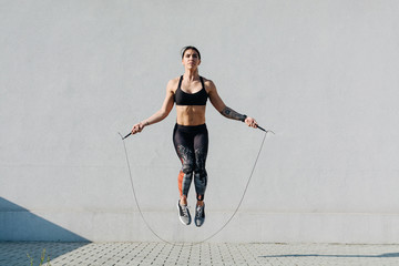 Young woman skipping ropes outdoors