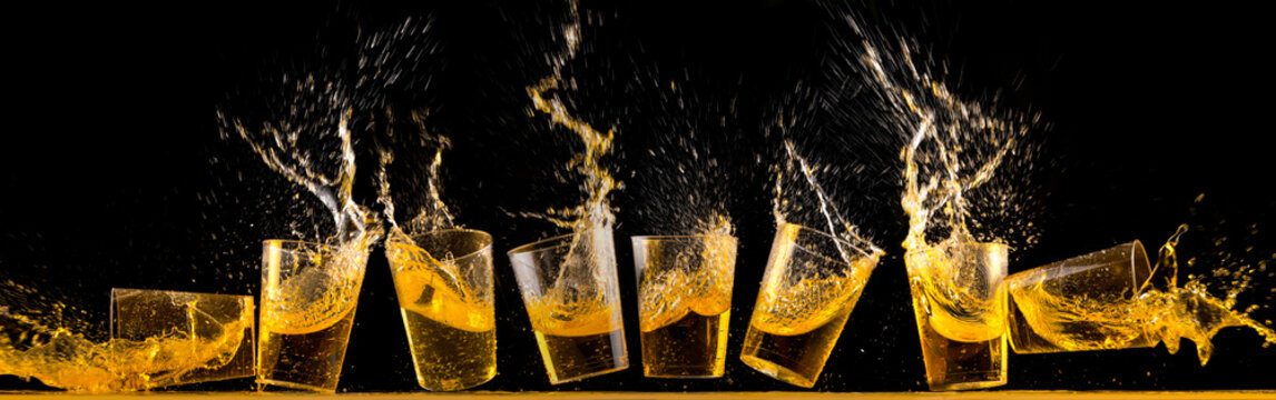 Eight golden tequila shots splashing