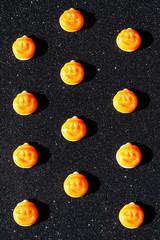 Jack-O-'Lantern Halloween candy on a sparkly black background.