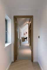 Evening view through an open door into the bedroom of a modern house.